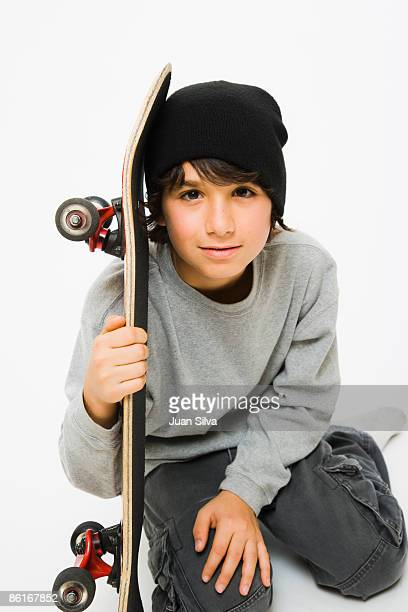Boy holding skateboard, portrait