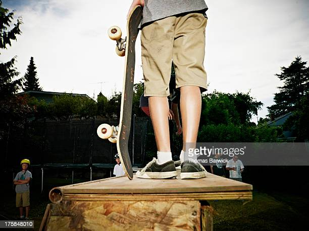 boy holding skateboard standing at top of halfpipe - half pipe stock pictures, royalty-free photos & images