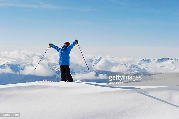 Boy holding ski poles in snow