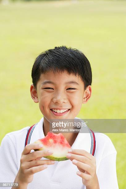 Boy holding slice of watermelon