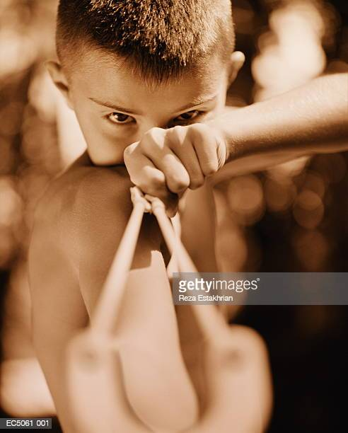 Boy (4-6) holding sling-shot (Digital Enhancement)