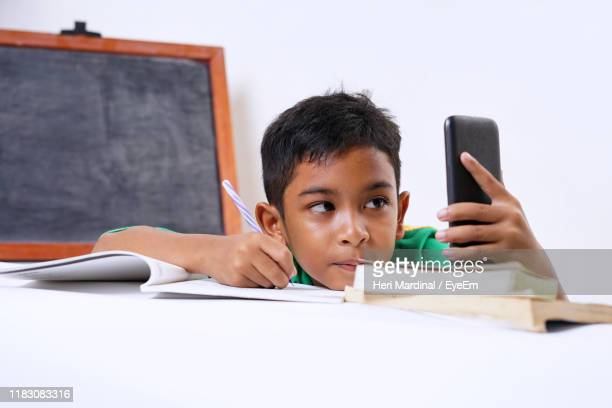 boy holding smart phone while writing in book on table - heri mardinal stock pictures, royalty-free photos & images