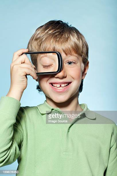 Boy holding smartphone over eye