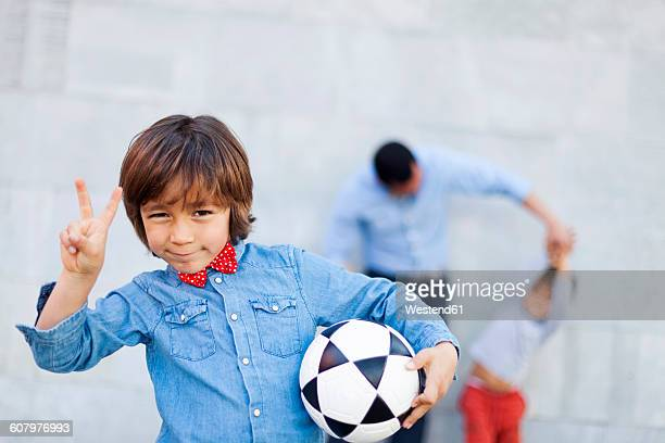 Boy holding soccer ball and making victory sign, family playing in background