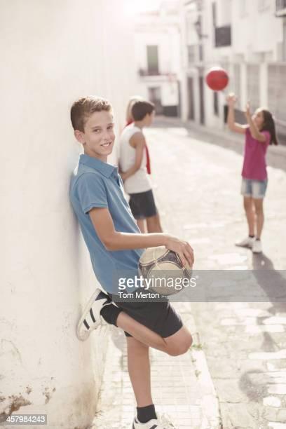 Boy holding soccer ball in alley