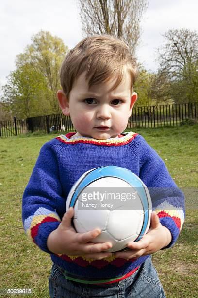 Boy holding soccer ball in backyard