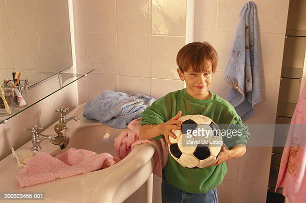 Boy (8-11) holding soccer ball in bathroom, elevated view