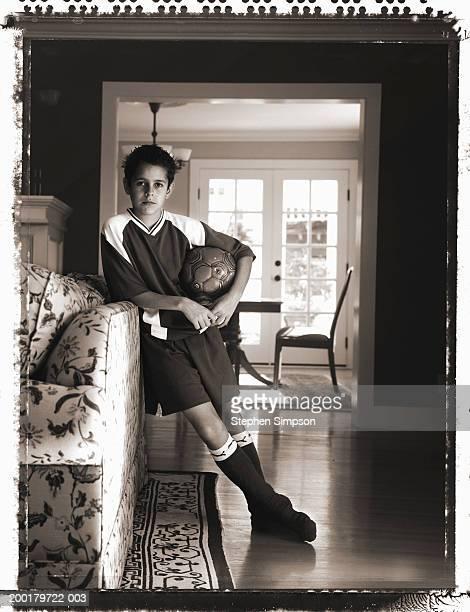 Boy (10-12) holding soccer ball, leaning on sofa (B&W)