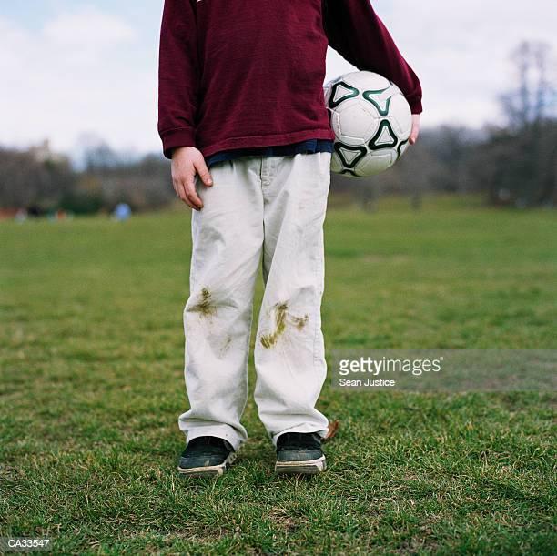 boy (7-9) holding soccer ball on field, low section - schmutzfleck stock-fotos und bilder