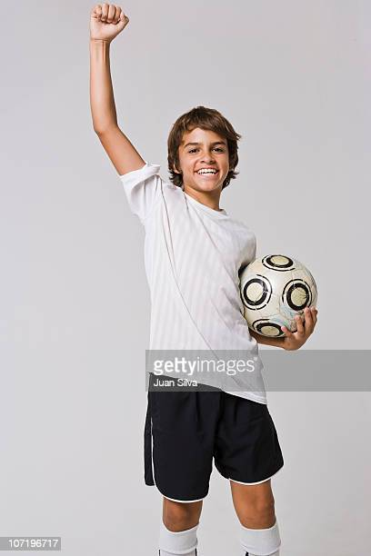 Boy holding soccer ball, smiling, portrait
