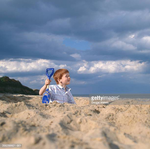 Boy (4-6) holding spade in sand pit on beach, smiling, ground view