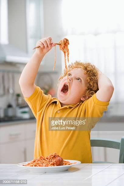 Boy (4-5) holding spaghetti, close-up, portrait