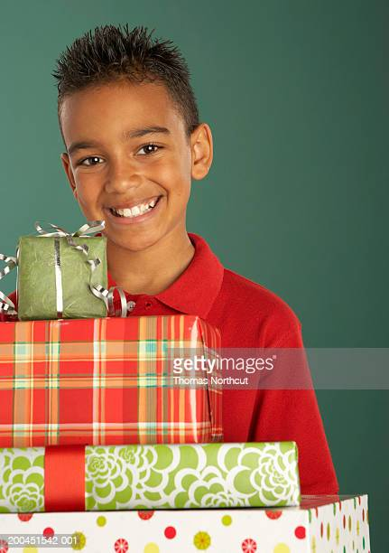 Boy (10-12) holding stack of gifts, smiling, portrait