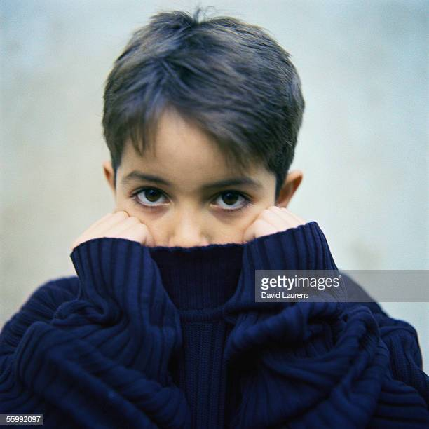 Boy holding sweater collar over mouth, portrait