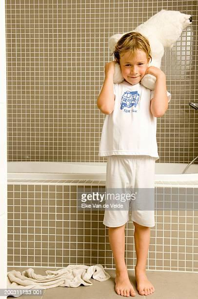 Boy (5-7) holding teddy bear beside bathtub, smiling, portrait