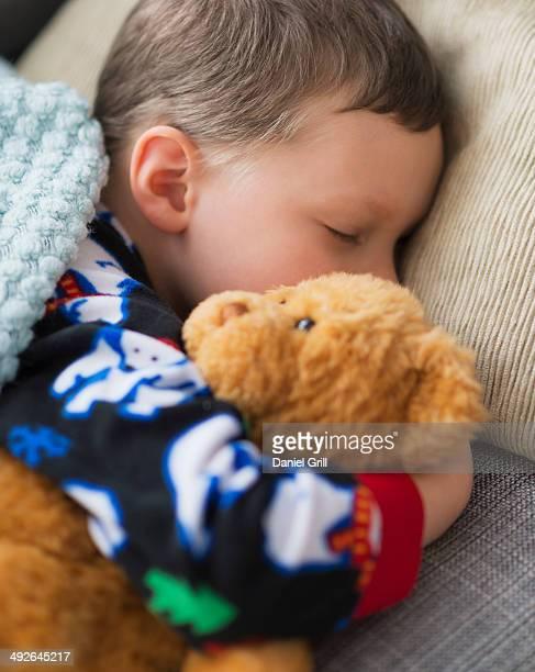 Boy (6-7) holding teddy bear during sleep, Jersey City, New Jersey, USA