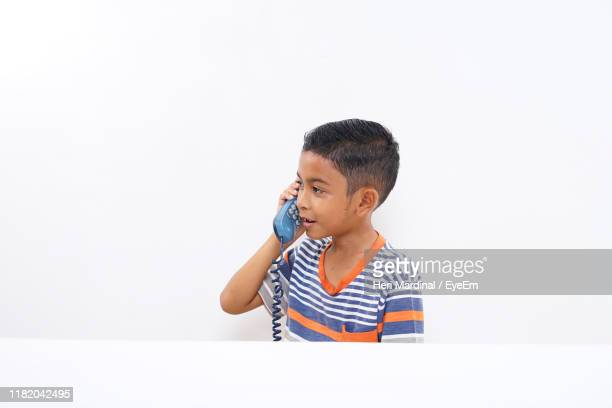 boy holding telephone receiver against white background - heri mardinal stock pictures, royalty-free photos & images