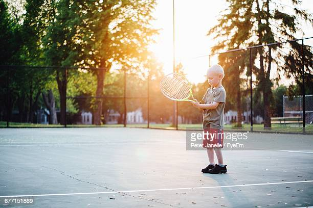 Boy Holding Tennis Racket While Standing At Court