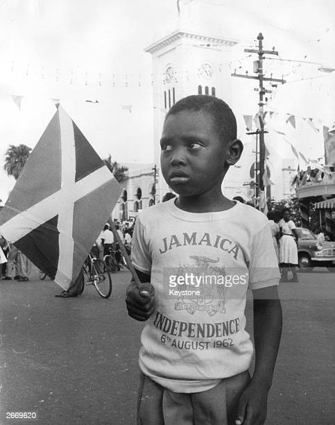 A boy holding the new Jamaican flag and wearing a commemorative teeshirt at the Independence celebrations