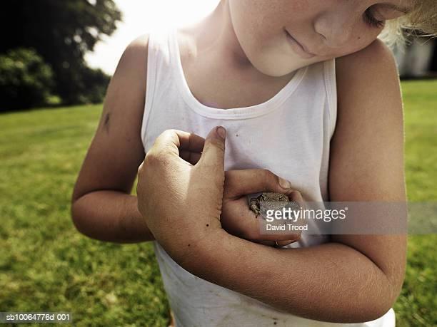 boy (8-9) holding toad in garden - sin mangas fotografías e imágenes de stock