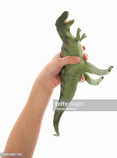 Boy (5-7) holding toy dinosaur, close-up of hand