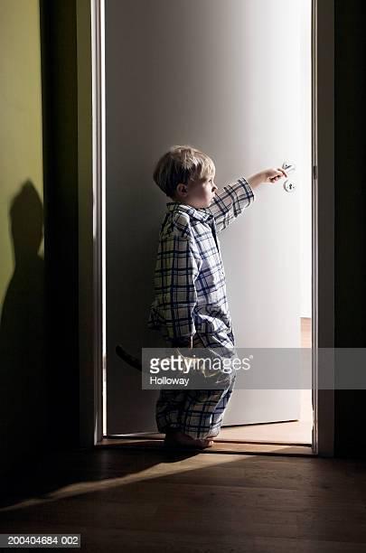 Boy (2-4) holding toy dinosaur standing in light of doorway