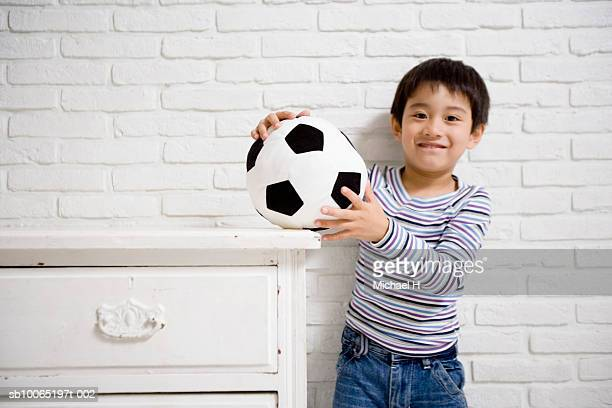 boy (4-5 years) holding toy soccer ball on wooden chest, standing against brick wall, portrait - 4 5 years stock pictures, royalty-free photos & images
