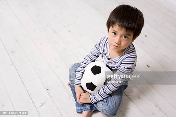 Boy (4-5 years) holding toy soccer ball sitting on wooden floor, elevated view, portrait