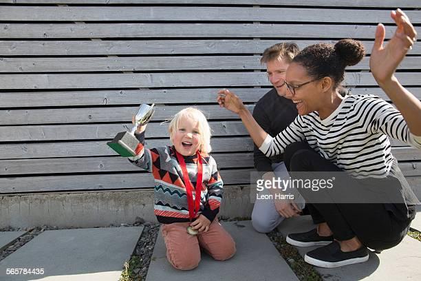 boy holding trophy, mother cheering - medaillengewinner stock-fotos und bilder