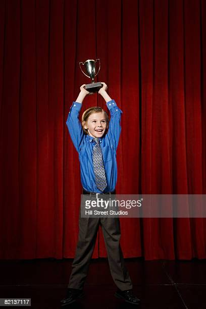 Boy holding trophy on stage