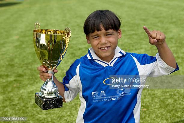 menino (7 e 9), segurando o troféu, apontando sorridente, retrato, elevada - trophy - fotografias e filmes do acervo