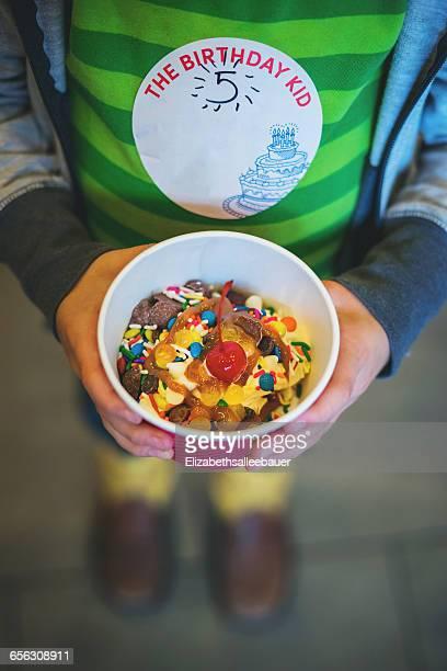 Boy holding tub of frozen yogurt with sprinkles