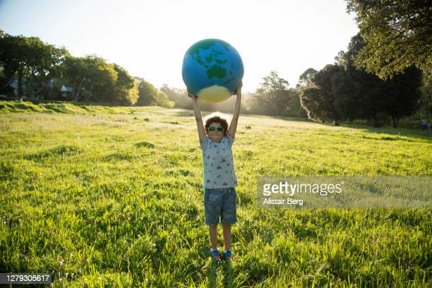 boy holding up a large globe outdoors - environmental issues stock pictures, royalty-free photos & images