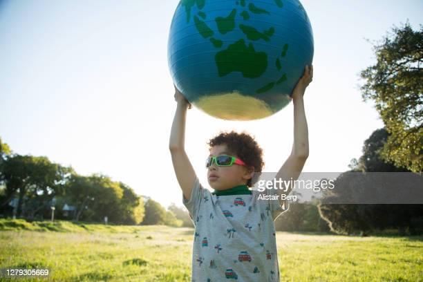boy holding up a large globe outdoors - activista fotografías e imágenes de stock