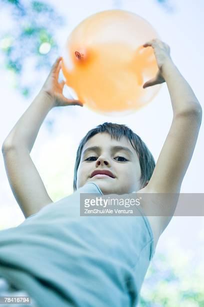 Boy holding up balloon