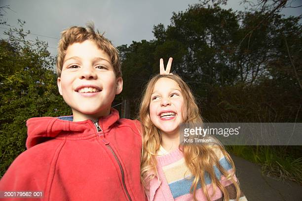 Boy (8-10) holding up bunny ears behind sister's head (5-7)