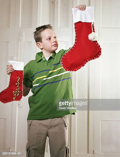 Boy (9-11) holding up Christmas stockings