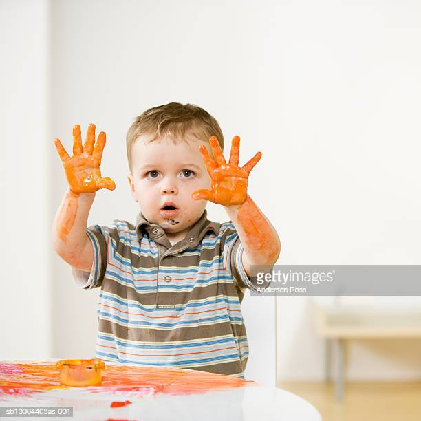 Boy (2-3) holding up hands covered with fingerpaint, at home