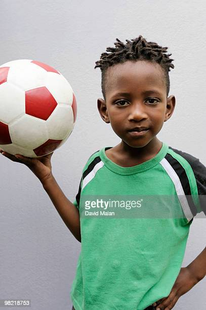 Boy holding up soccer ball, Cape Town, Western Cape Province, South Africa