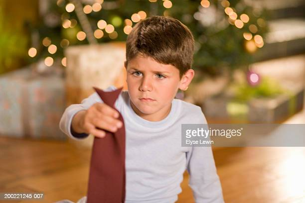 Boy (4-6) holding up tie, Christmas tree in background