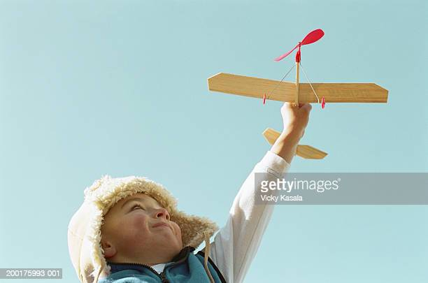 Boy (3-5) holding up toy airplane, low angle view