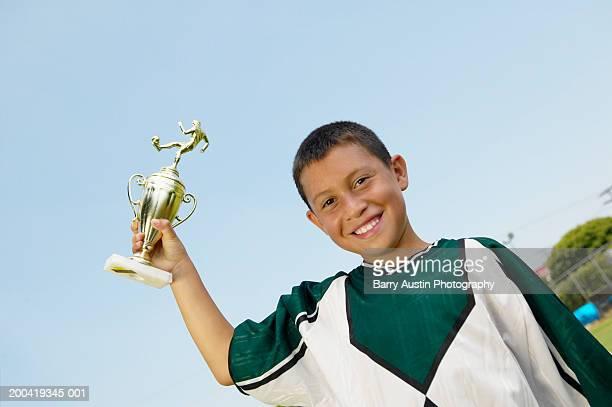 boy (7-9) holding up trophy, smiling, portrait, low angle view - trophy - fotografias e filmes do acervo