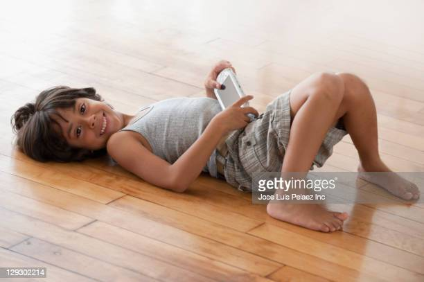 Boy holding video game and laying on floor