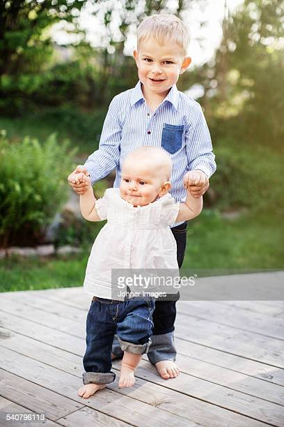 Boy holding walking sister