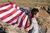 boy holding waving us flag beeng