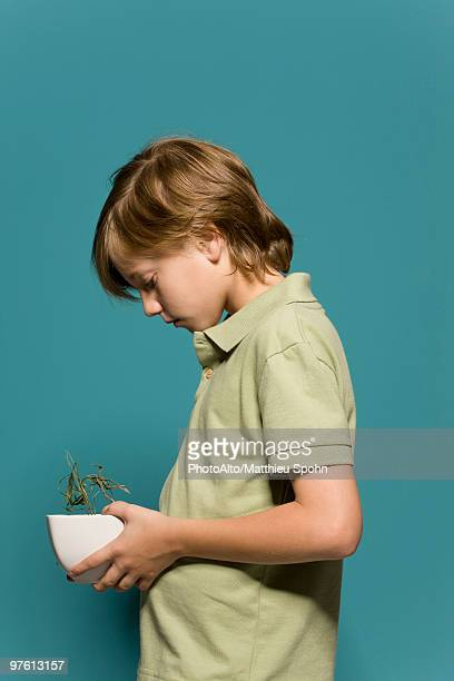 Boy holding wilted potted plant, head down