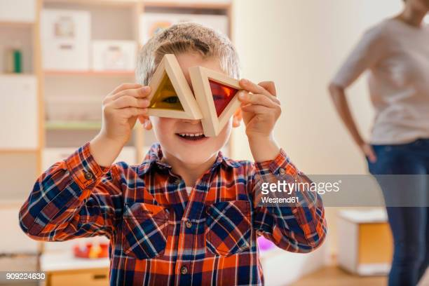 boy holding wooden and colorful blocks before his eyes in kindergarten - kindergarten stock-fotos und bilder