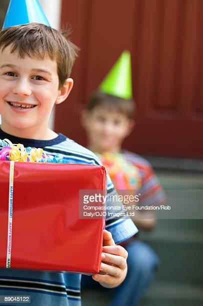 """boy holding wrapped gift - """"compassionate eye"""" - fotografias e filmes do acervo"""