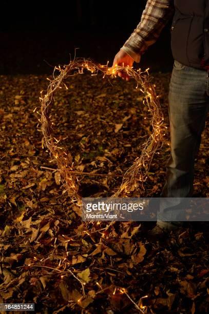 Junge holding Kranz von Weihnachtsbeleuchtung im Freien
