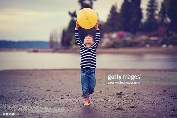boy holding yellow ball on a beach